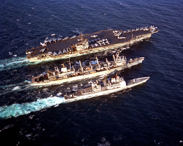 The fast combat support ship USS DETROIT (AOE-4), center, conducts an underway replenishment with the aircraft carrier USS JOHN F. KENNEDY (CV-67), top, and the guided missile cruiser USS SAN JACINTO (CG-56) during Operation Desert Storm