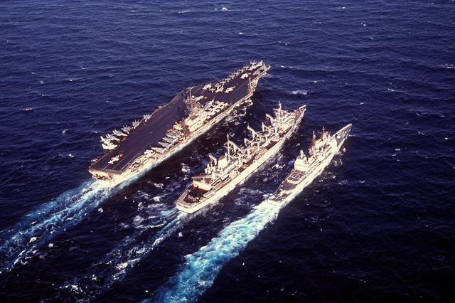 The fast combat support ship USS DETROIT (AOE-4) is flanked by the aircraft carrier USS JOHN F. KENNEDY (CV-67) left, and the guided missile cruiser USS SAN JACINTO (CG-56) as the ships conduct an underway replenishment during Operation Desert Storm