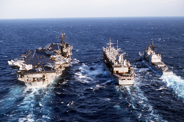 The fast combat support ship USS DETROIT (AOE-4) is flanked by the aircraft carrier USS JOHN F. KENNEDY (CV-67), left, and the guided missile cruiser USS SAN JACINTO (CG-56) as the ships conduct an underway replenishment during Operation Desert Storm