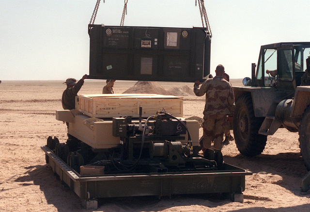 A crane is used to lift part of the shipping container off of a Mark 154 mine clearance kit as the kit is readied for installation on an AAVP-7A1 amphibious assault vehicle by Marine assigned to Task Force Breach Alpha during Operation Desert Storm. The Marines are from the 2nd Combat Engineer Battalion, 2nd Marine Division.