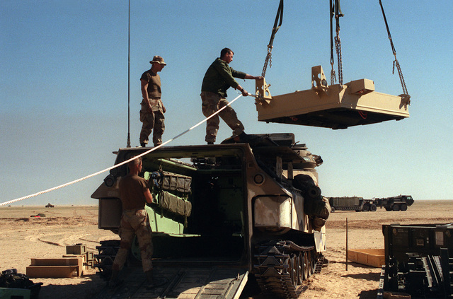 A Marine assigned to Task Force Breach Alpha stands atop an AAVP-7A1 amphibious assault vehicle as he guides a Mark 154 mine clearance kit into position over the vehicle during Operation Desert Storm. The Marines are from the 2nd Combat Engineer Battalion, 2nd Marine Division.