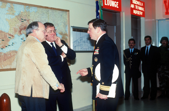 An officer speaks with Secretary of Defense Richard Cheney and a civilian official during Cheney's brief stopover at the air station. Cheney and GEN. Colin Powell, chairman of the Joint Chiefs of STAFF, are en route to the Middle East on a fact finding mission during Operation Desert Storm