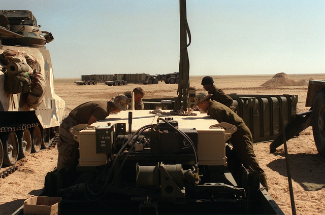 Four Marines assigned to Task Force Breach Alpha prepare to attach lifting chains to a Mark 154 mine clearance kit as they ready it for installation on an AAVP-7A1 amphibious assault vehicle during Operation Desert Storm. The Marines are from the 2nd Combat Engineer Battalion, 2nd Marine Division.