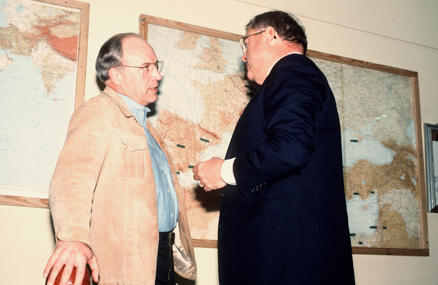 Secretary of Defense Richard Cheney speaks with an official during a brief stopover at the air station. Cheney and GEN. Colin Powell, chairman of the Joint Chiefs of STAFF, are en route to the Middle East on a fact finding mission during Operation Desert Storm
