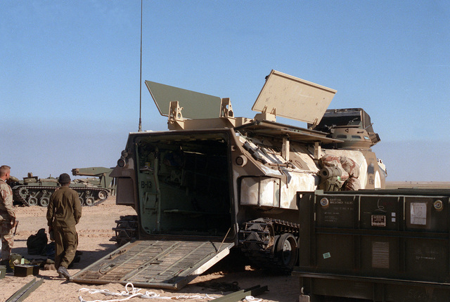 Two Marines assigned to Task Force Breach Alpha complete the installation of a Mark 154 mine clearance kit on an AAVP-7A1 amphibious assault vehicle during Operation Desert Storm. The Marines are from the 2nd Combat Engineer Battalion, 2nd Marine Division.