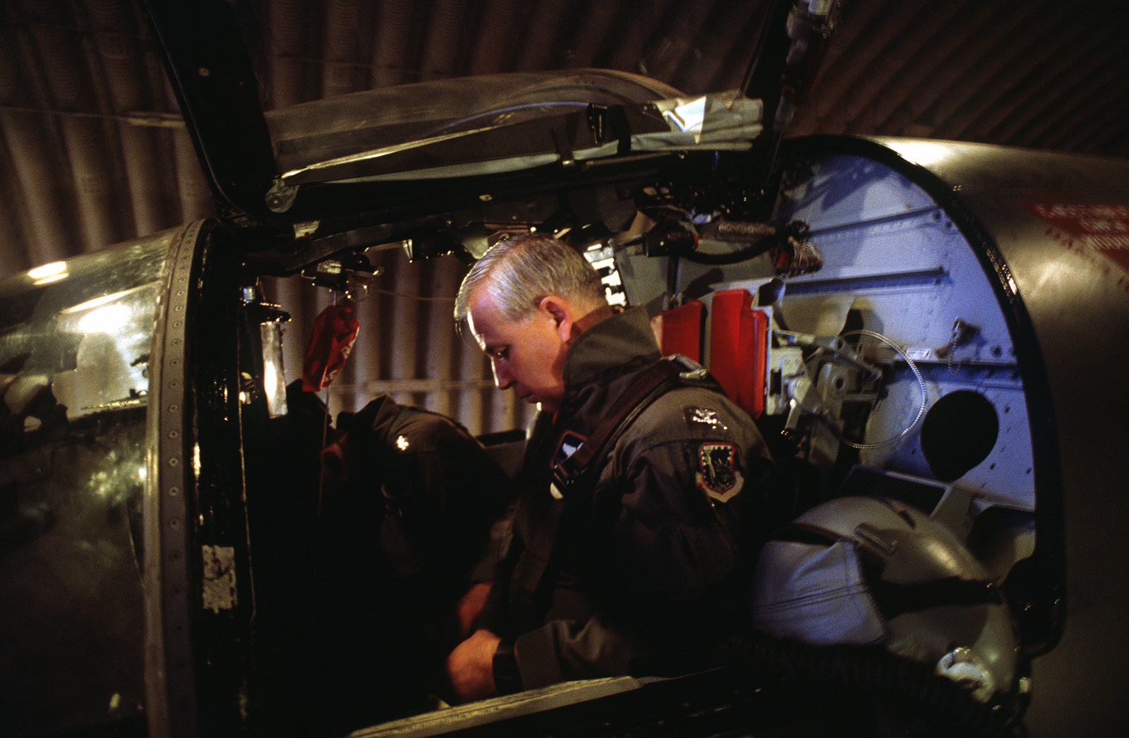 COL. Tom Lennon, 48th Tactical Fighter Wing commanding officer, checks his flight gear in the cockpit of an F-111F aircraft as he prepares to deploy to Saudi Arabia in support of Operation Desert Shield