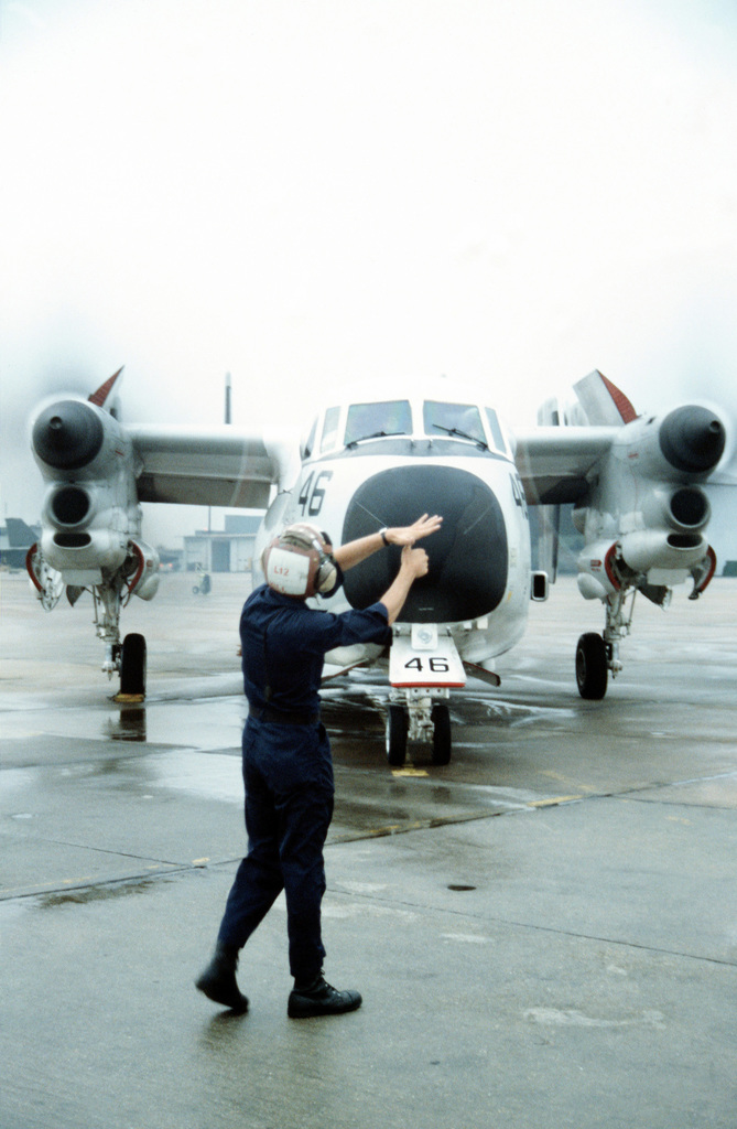 A ground crew member signals the pilot of a Fleet Logistics Support Squadron 40 (VRC-40) C-2A Greyhound Carrier On-board Delivery (COD) aircraft as the plane prepares to take off with a load of passengers and mail bound for the nuclear-powered aircraft carrier USS DWIGHT D. EISENHOWER (CVN-69)