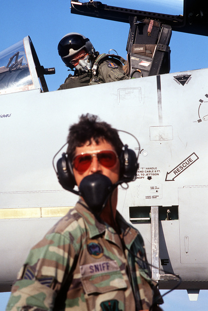 A 33rd Tactical Fighter Wing (33rd TFW) maintenance crew member stands by as COL. Rick N. Parsons, commander, 33rd TFW, checks his survival gear in the cockpit of his F-15C Eagle aircraft prior to deploying to the Middle East in support of Operation Desert Shield