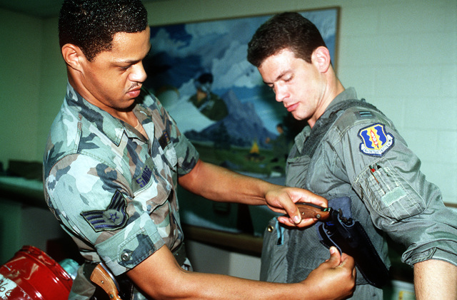A 58th Tactical Fighter Wing pilot receives a sidearm prior to deploying to the Middle East in support of Operation Desert Shield