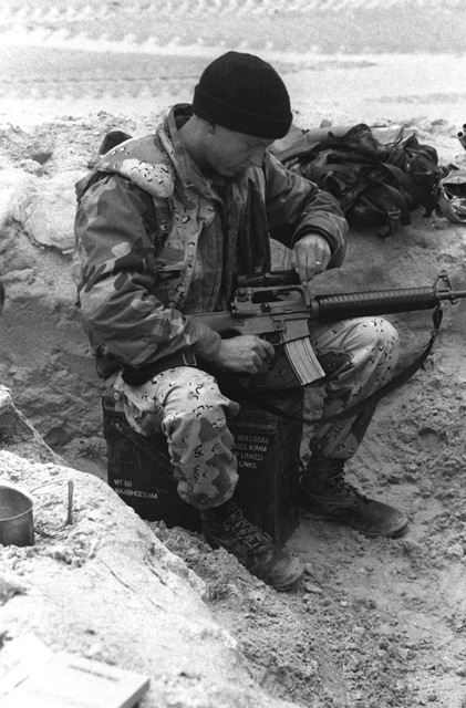 A member of D Co., 1ST Light Armored Infantry (LAI) Battalion, 1ST Marine Division, checks his 5.56mm M-16A2 rifle during Operation Desert Storm.The rifle is fitted with a telescopic sight