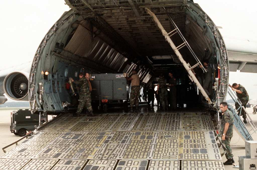 Ground crew members secure equipment inside a Military Airlift Command C-5 Galaxy aircraft for deployment to Saudi Arabia in support of Operation Desert Shield
