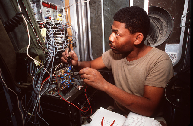 A soldier sets up a communications system during Operation Desert Shield