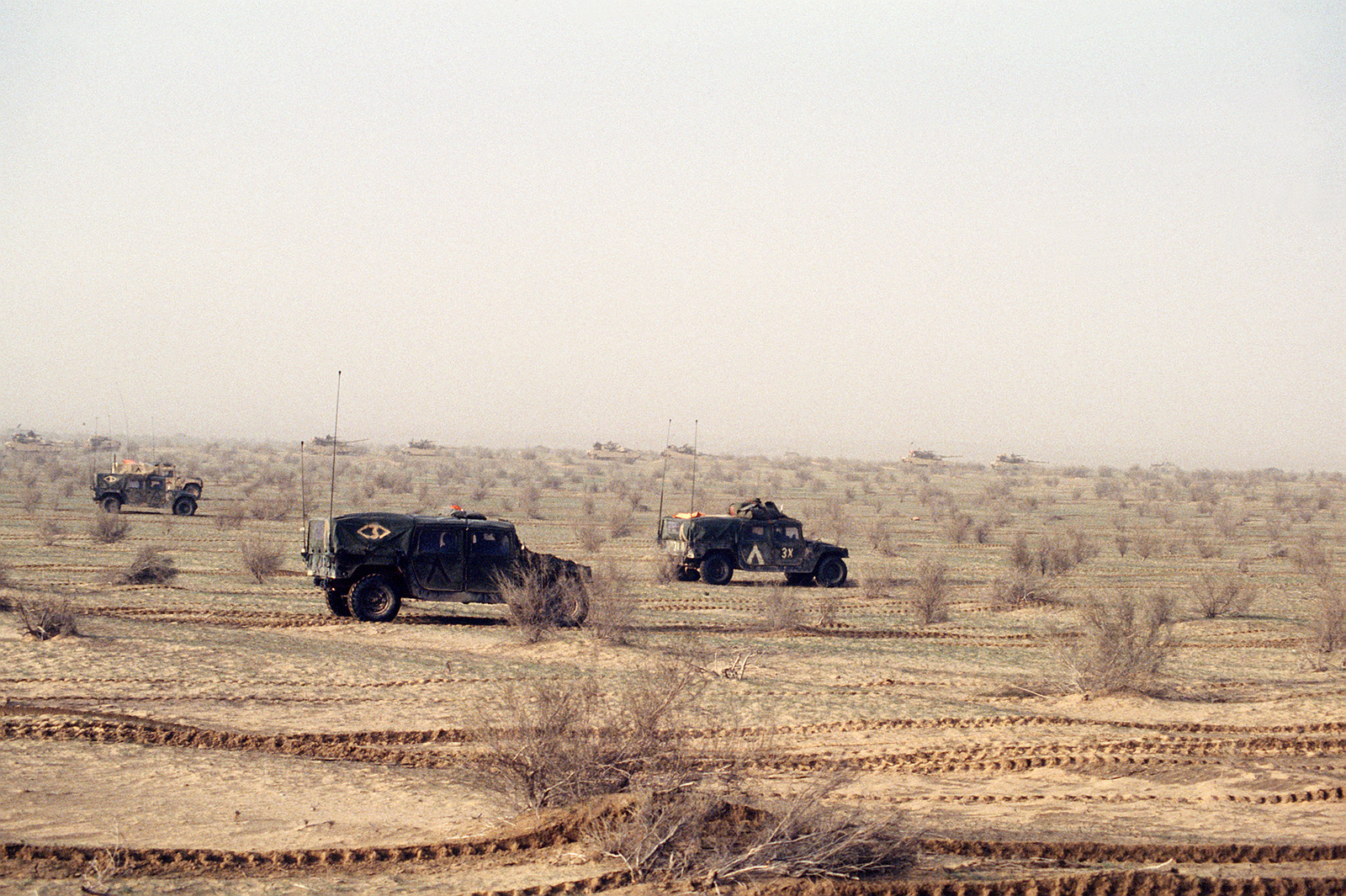 M-998 high-mobility, multipurpose, wheeled vehicles of the 1ST Armored Division, VII Corps, Augsburg, Germany, advance on Iraqi positions during Operation Desert Storm. On the horizon are VII Corps tanks