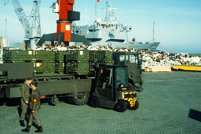 A forklift unloads ordnance containers from a truck of the Dutch army's 812th Transportation Group. The ordnance has been transported to the pier for redeployment to the United States in the aftermath of Operation Desert Storm