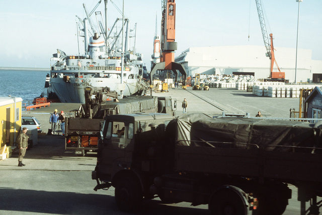 Members of the Dutch army's 812th Transportation Group position DAF YA 4-ton trucks on a pier at Eemshaven Port. The trucks are carrying ordnance which will be loaded aboard the merchant ship USNS DEL VALLE for redeployment to the United States in the aftermath of Operation Desert Storm