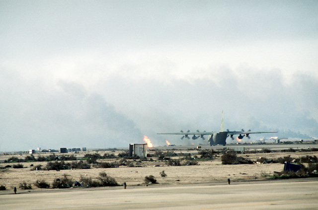 A C-130H Hercules transport aircraft from the 328th Tactical Airlift Squadron, Little Rock Air Force Base, Ark., lands at Kuwait International Airport after the retreat of Iraqi forces from Kuwait during Operation Desert Storm. In the background are burning oil wells set ablaze by retreating Iraqi troops.
