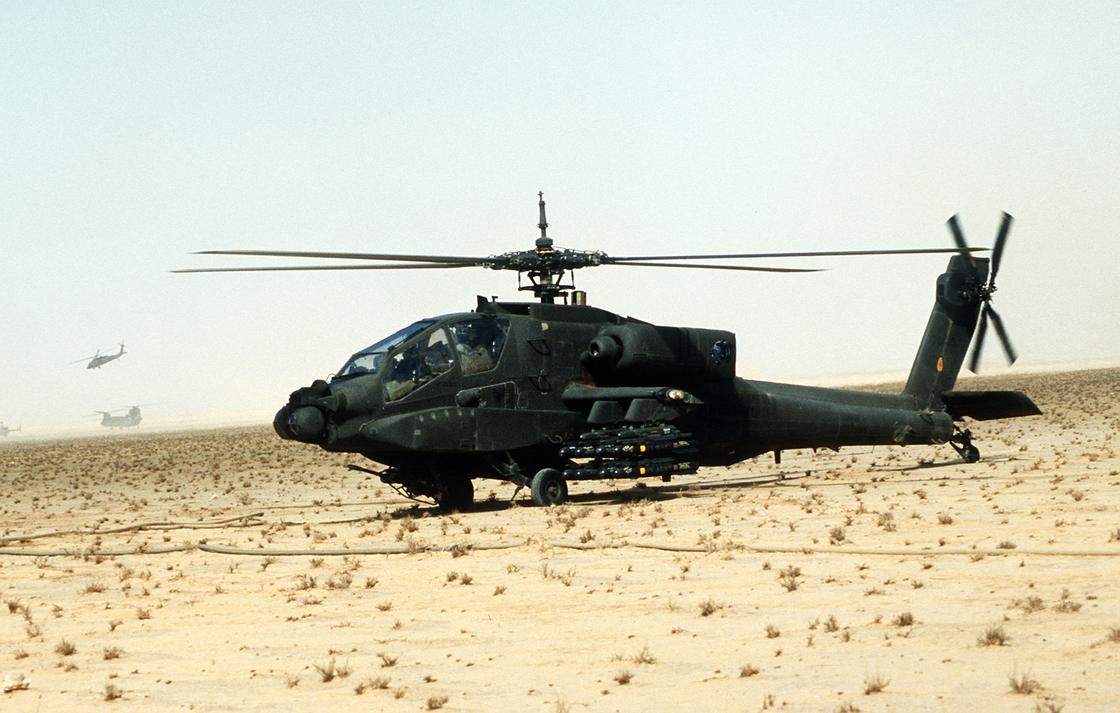 An AH-64A Apache anti-tank helicopter of the XVIII Airborne Corps, armed with AGM-114A Hellfire anti-tank missiles, is prepared for a mission during Operation Desert Storm