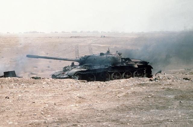 A demolished Iraqi T-55 main battle tank stands on a battlefield after being destroyed by Allied forces during Operation Desert Storm