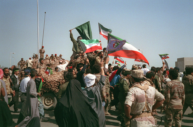 Civilians and coalition military forces wave Kuwaiti, Saudi Arabian and other flags as they celebrate the retreat of Iraqi forces from Kuwait as a result of Operation Desert Storm