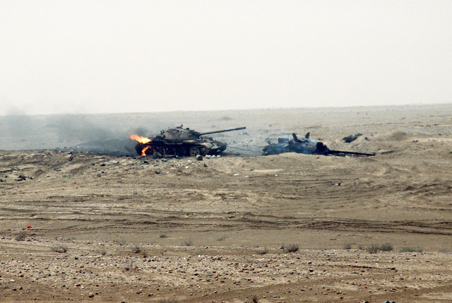 Two Iraqi T-55 main battle tanks damaged during Operation Desert Storm. The rear tank was attempting to tow the other one, as evidenced by the cable linking them. Both tanks are still burning