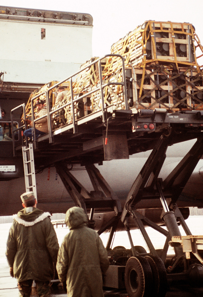 A K-loader positions crates of 155mm propellant canisters for loading onto a Canadian DC-8 aircraft. The material is being shipped to Saudi Arabia in the aftermath of Operation Desert Storm