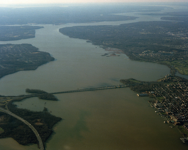 An aerial view of a portion of the Potomac River immediately south of Washington, District of Columbia, spanned at this point by the Woodrow Wilson Memorial Bridge. Maryland is at left, Virginia is at right