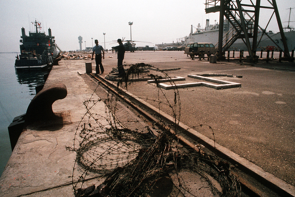 Barbed wire lies on the pier after being retrieved by a multinational explosives ordnance disposal (EOD) team during a sweep of the harbor area in an effort to locate mines left by retreating Iraqi forces. The U.S. Army barge CHATEAU-THIERRY, in the foreground, at left, and the Army logistic support vessel LT. GEN. WILLIAM B. BUNKER (LSV-4), are docked at the pier. A Helicopter Mine Countermeasures Squadron 14 (HM-14) MH-53E Sea Dragon helicopter stands on the pier in the background
