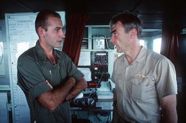 CAPT. Douglas C. Bauer, center, Naval historian, converses with the officer-in-charge of a commando detachment deployed aboard the French destroyer FS JEAN DE VIENNE (D-643). The French ship, part of the Maritime Interdiction Force, has been assisting in the enforcement of U.S. trade sanctions against Iraq during Operation Desert Storm