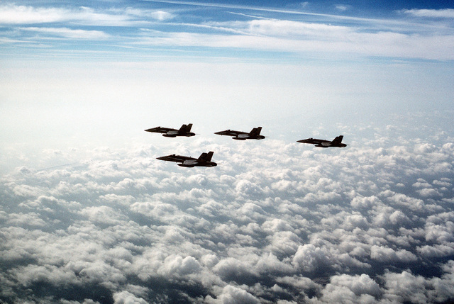 Four F/A-18A Hornet aircraft from Strike Fighter Squadron 137 (VFA-137) pass over the clouds during a training flight out of Naval Air Station, Cecil Field, Florida. VFA-137 and the other squadrons of Carrier Air Wing 6 (CVW-6) are to depart at the end of May on a Mediterranean deployment aboard the aircraft carrier USS FORRESTAL (CV-59)