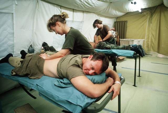 Marine Corps Reserve CAPT. Walter Gray of Marine Light Helicopter Squadron 767 (HML-767), a patient at Fleet Hospital 15, receives a friction massage from Hospital Corpsman 2nd Class Valerie Gilges in the physical therapy tent. The hospital was established to support Operation Desert Shield and Operation Desert Storm