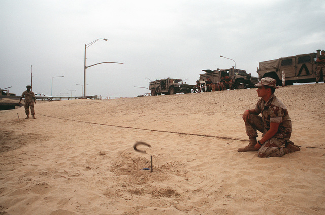 Marines toss horseshoes to pass the time during the cease fire at the conclusion of Operation Desert Storm. The men are waiting for their vehicles to be cleaned before redeployment