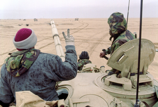 Members of the Coalition forces drive a T-72 main battle tank along a channel cleared of mines as one of the soldiers gives a victory sign during Operation Desert Storm.