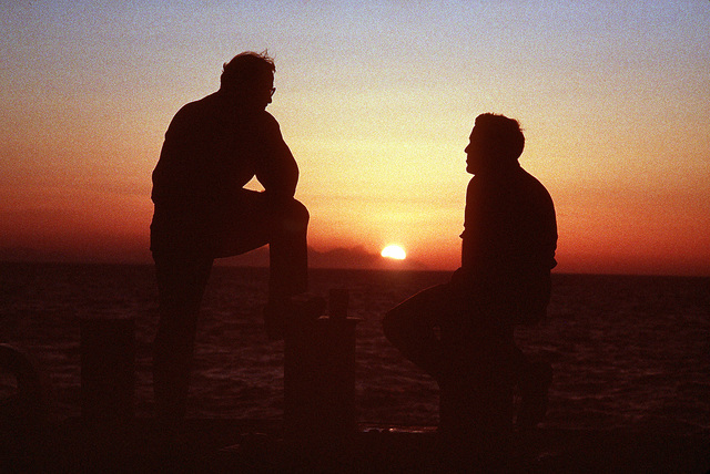 SENIOR CHIEF Machinist's mate Dennis Cutler and Boilerman Technician 2nd Class Thomas Coppie converse as they watch the sun rise over the Sinai Peninsula from the deck of the guided missile destroyer USS WILLIAM V. PRATT (DDG-44). The PRATT, flagship of the Maritime Interdiction Force, has been enforcing U.N. trade sanctions against Iraq during Operation Desert Storm