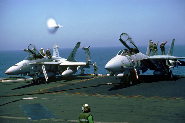 The moisture in the air around a Fighter Squadron 102 (VF-102) F-14A Tomcat aircraft condenses into water vapor as the aircraft breaks the sound barrier while passing the aircraft carrier USS AMERICA (CV-66). In the foreground are a Strike Fighter Squadron 86 (VFA-86) F/A-18C Hornet aircraft, left, and a VF-102 Tomcat. The AMERICA is on station in the Red Sea following Operation Desert Storm.
