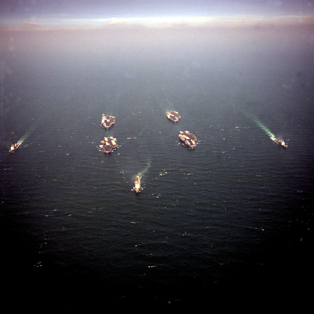An aerial view of the ships of Battle Force Zulu underway at the conclusion of Operation Desert Storm. The guided missile cruisers include the USS BUNKER HILL (CG-52), the USS NORMANDY (CG-60), and the USS LEYTE GULF (CG-55). Aircraft carriers include the USS MIDWAY (CVB-41), the USS RANGER (CV-61), the USS AMERICA (CV-66) and the nuclear-powered aircraft carrier USS THEODORE ROOSEVELT (CVN-71)