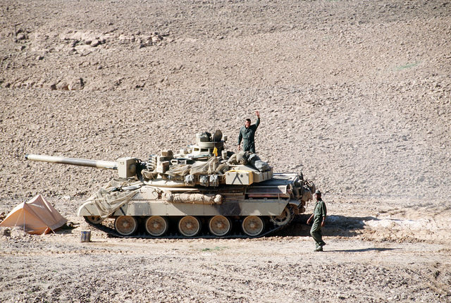A crew member waves to the camera from the back of his AMX-30 main battle tank of the French 6th Light Armored Division bivouaced near Al-Salman during Operation Desert Storm.