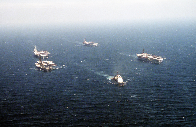 The four aircraft carriers of Battle Force Zulu travel in formation behind the guided missile cruiser USS BUNKER HILL (CG-52) during Operation Desert Storm. The carrier include the USS MIDWAY (CV-41), the USS RANGER (CV-61), the USS AMERICA (CV-66) and the nuclear-powered aircraft carrier USS THEODORE ROOSEVELT (CVN-71)