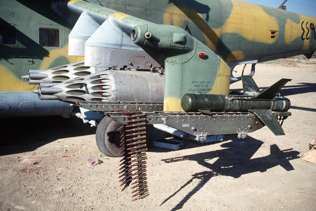 A close-up view of the left side winglet of an Iraqi MIL Mi-24 Hind-D assault helicopter abandoned during Operation Desert Storm. The ordnance is two UV-32-57 rocket pods, each containing 32 S-5 57mm rockets, and an AT-2 Swatter anti-tank missile. A belt of 12.7mm machine gun ammunition is draped over the missile launch rail.