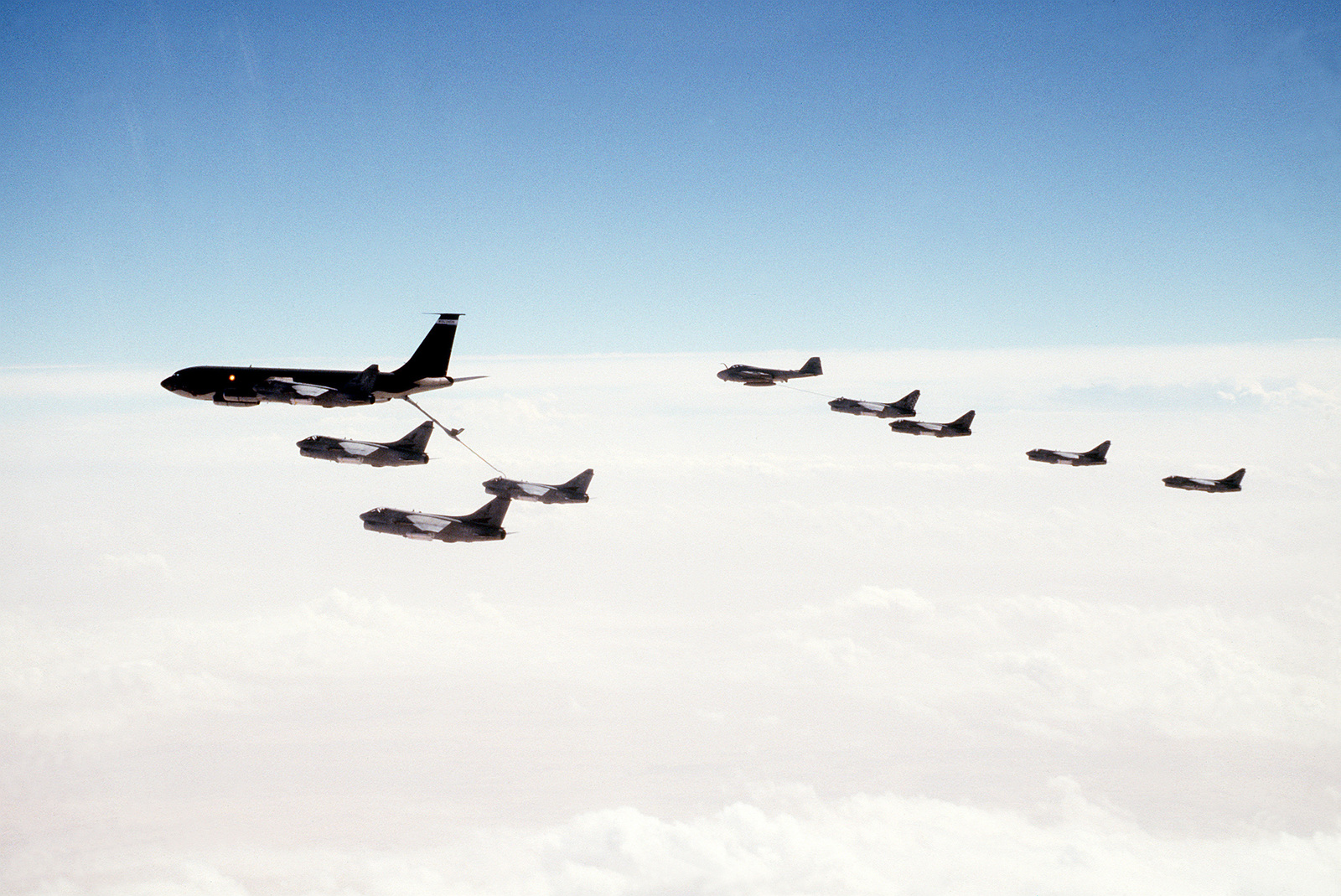 A KC-135 Stratotanker aircraft, foreground, and an A-6E Intruder aircraft, background, refuel A-7E Corsair II aircraft over the Red Sea during Operation Desert Storm.
