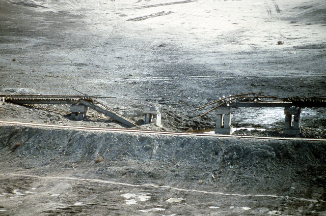 A railroad bridge lies in ruins near the Arramaylan Refinery in the aftermath of an Allied attack during Operation Desert Storm.