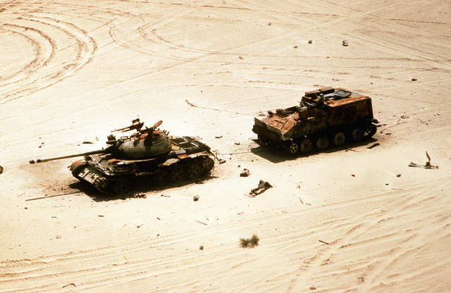 An Iraqi T-55 main battle tank and the YW-750 armored personnel carrier that it had been towing lie in the desert after being abandoned by Iraqi forces during Operation Desert Storm