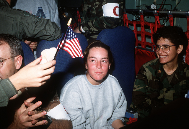 SPEC. Melissa Rathbun-Nealy, the first female to be taken as a prisoner of war during Operation Desert Storm, receives a miniature American flag from a flight nurse aboard a C-141 Starlifter aircraft. Rathbun-Nealy, five other American POWs, and one Italian POW were released from captivity on March 4 and are scheduled for medical examination and treatment aboard the hospital ship USNS MERCY (T-AH-19)