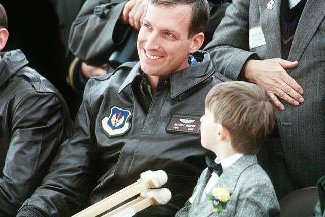 U.S. Air Force CAPT. William F. Andrews sits beside his son while listening to a speech by Secretary of Defense Richard Cheney welcoming him and other former prisoners of war home to the United States. Andrews was one of a number of POWs held captive by Iraqi forces during Operation Desert Storm.