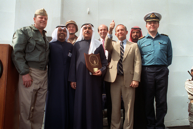 Dignitaries gather aboard the command ship USS LA SALLE (AGF-3) following a ceremony marking the re-opening of Ash Shuaybah's port facility after a multinational effort to clear the mines laid by Iraqi forces during their occupation of Kuwait. Among the dignitaries are Rear Adm. Raynor A.K. Taylor, left, commander, U.S. Navy Middle East Force; CAPT. Abdel-Rahman Naibari, fourth from left, Kuwaiti ports chief; and U.S. Ambassador to Kuwait Edward Gnehm, third from right