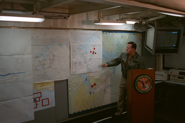 Rear Adm. Raynor A.K. Taylor, commander, Middle East Force, points out strategic areas on a map while conducting a news conference prior to a ceremony marking the re-opening of Ash Shuaybah's port facility during Operation Desert Storm. The port is being reopened after a multinational effort to clear the mines laid by Iraqi forces during their occupation of Kuwait