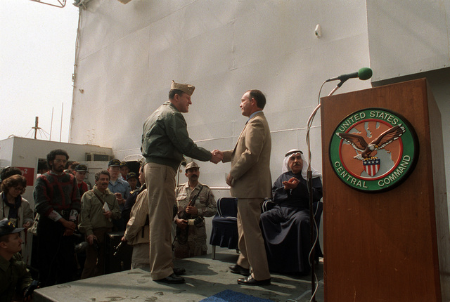Rear Adm. Raynor A.K. Taylor, left, commander, U.S. Navy Middle East Force, shakes hands with Edward Gnehm, U.S. ambassador to Kuwait, speaks to guests aboard the command ship USS LA SALLE (AGF-3) during a ceremony marking the re-opening of Ash Shuaybah's port facility after a multinational effort to clear the mines laid by Iraqi forces during their occupation of Kuwait. Kuwaiti ports chief CAPT. Abdel-Rahman Naibari is seated at center