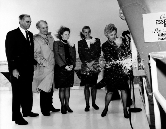 Lynne Cheney, right, sponsor of the amphibious assault ship ESSEX (LHD-2), breaks a bottle of champagne across its bow to christen the ship. Looking on are, from left: Jerry St. Pe, president of Ingalls Shipbuilding; Secretary of Defense Dick Cheney; and Elizabeth and Mary Cheney, maids of honor