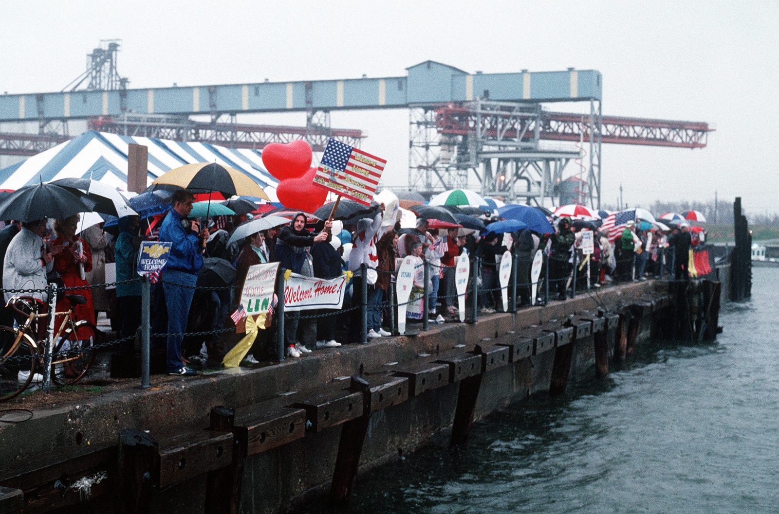 Family and friends of crew members aboard the combat stores ship USS SYLVANIA (AFS-2) wait in the rain to welcome their loved ones as the ship returns from deployment in the Persian Gulf during Operation Desert Storm