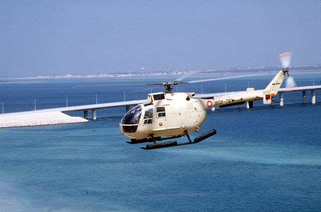 A BO-105 helicopter of Bahrain flies inland near a causeway in the aftermath of Operation Desert Storm.