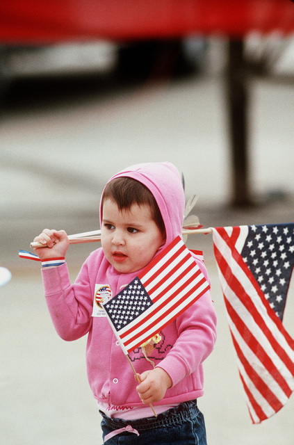 A child clutches the American flag during a ceremony to welcome home LT. Robert Wetzel, LT. Lawrence Slade, and LT. Jeffrey Zaun. The three Navy pilots' aircraft were shot down over Iraq during Operation Desert Storm and the men held as prisoners of war until their release on March 4th